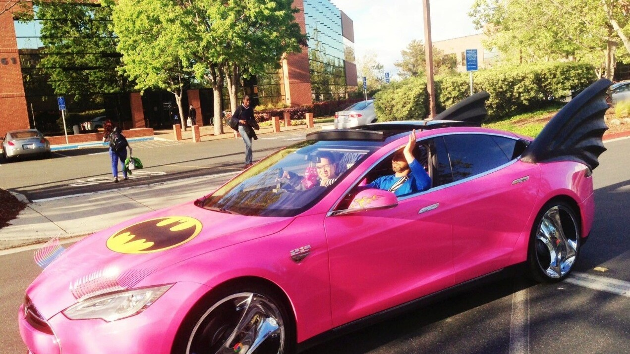 Sergey Brin in Google Glass driving a pink Tesla Batmobile with eyelashes
