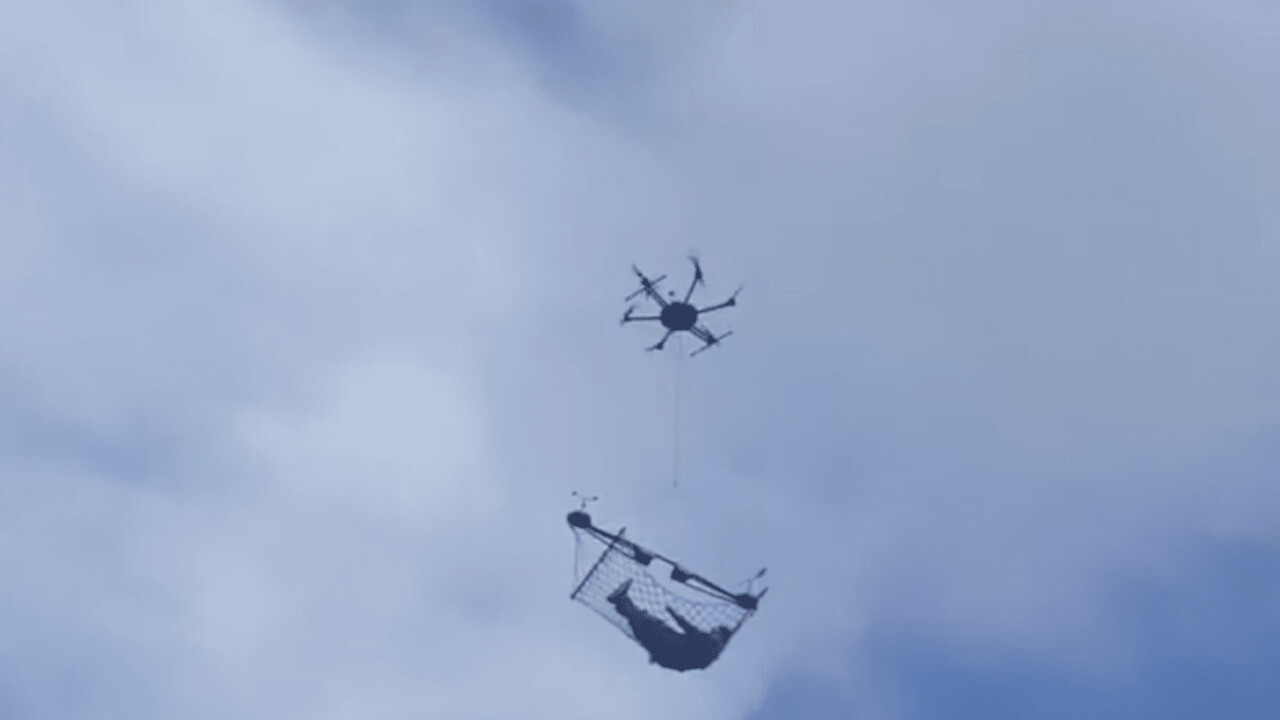 Drone carries what appears to be a man in a hammock through town